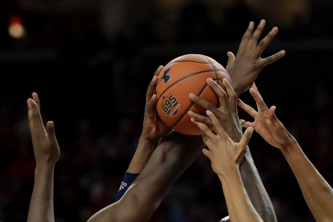 The hands of Rhode Island forward Cyril Langevine are seen holding the ball as Maryland forward Makhi Mitchell and guard Aaron Wiggins defend during the second half of an NCAA college basketball game, Saturday, Nov. 9, 2019, in College Park, Md. Maryland won 73-55. (AP Photo/Julio Cortez)