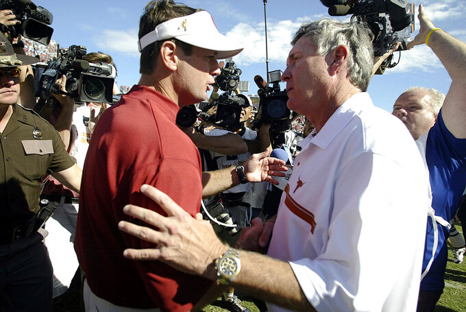 FILE - In this Oct. 8, 2005, file photo, Texas coach Mack Brown, right, greets Oklahoma coach Bob Stoops after the Longhorns 45-12 win in Dallas. The annual Texas-Oklahoma rivalry game in Dallas decided the Big 12 more often than not. Both teams were nationally ranked in nine of the ten meetings. Oklahoma won the first five from 2000-04 but Texas bounced back by winning four of the last five. (AP Photo/Matt Slocum, FIle)
