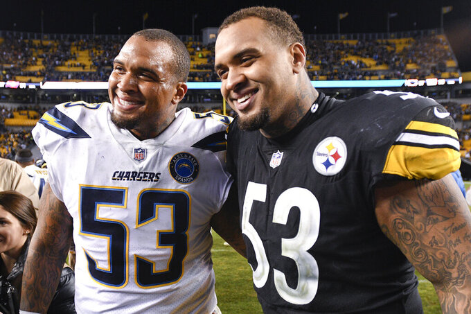 FILE - In this Dec. 2, 2018, file photo, Pittsburgh Steelers center Maurkice Pouncey, right, and his brother, Los Angeles Chargers center Mike Pouncey pose after playing against each other in an NFL football game in Pittsburgh. The twin brothers announced their retirement from professional football on Friday, Feb. 12, 2021. (AP Photo/Don Wright, File)