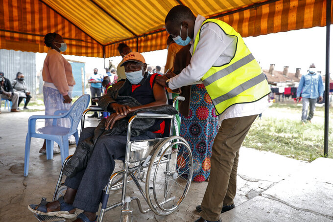 A Kenyan man receives a dose of the AstraZeneca coronavirus vaccine donated by Britain, at the Makongeni Estate in Nairobi, Kenya Saturday, Aug. 14, 2021. In late June, the international system for sharing coronavirus vaccines sent about 530,000 doses to Britain – more than double the amount sent that month to the entire continent of Africa. It was the latest example of how a system that was supposed to guarantee low and middle-income countries vaccines is failing, leaving them at the mercy of haphazard donations from rich countries. (AP Photo/Brian Inganga)