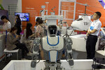 Visitors to the 21st China Beijing International High-tech Expo look at robots and helicopter drone displayed in Beijing, China, Thursday, May 17, 2018. The Trump administration has threatened to impose tariffs on up to $150 billion in Chinese imports to punish Beijing over trade practices requiring American companies to hand over technology in exchange for access to the Chinese market. China has counterpunched by targeting $50 billion in U.S. products.(AP Photo/Ng Han Guan)