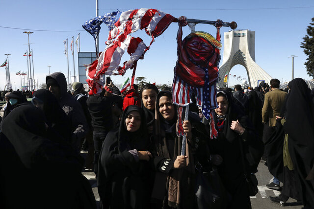 Demonstrators hold a caricature of President Donald Trump with a tattered U.S. flag in front of Azadi (Freedom) monument tower during a rally celebrating the 41st anniversary of the Islamic Revolution, at Azadi (Freedom) Street, in Tehran, Iran, Tuesday, Feb. 11, 2020. Hundreds of thousands across Iran mark the anniversary of the 1979 Islamic Revolution amid some of the highest tensions with Washington in decades while Iran's president denounces America and urges the crowds to vote in parliamentary elections this month. (AP Photo/Vahid Salemi)