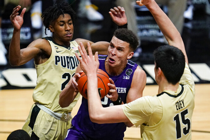 Northwestern forward Pete Nance (22) cuts between Purdue guard Jaden Ivey (23) and center Zach Edey (15) during the first half of an NCAA college basketball game in West Lafayette, Ind., Saturday, Feb. 6, 2021. (AP Photo/Michael Conroy)