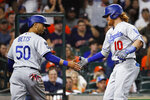 Los Angeles Dodgers' Justin Turner, right, slaps hands with Mookie Betts after hitting a two-run home run off Houston Astros starting pitcher Zack Greinke during the fourth inning of a baseball game Tuesday, May 25, 2021, in Houston. (Kevin M. Cox/The Galveston County Daily News via AP)