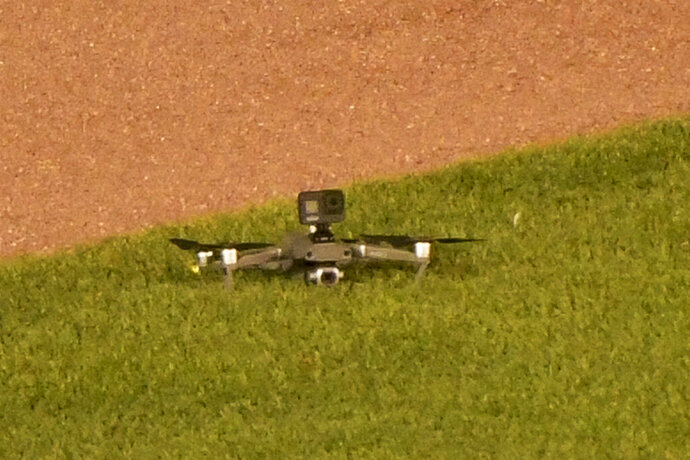 A drone lies on the grass after it landed in center field, before taking off again and flying out of the stadium, during the fifth inning of a baseball game between the Chicago Cubs and the Cleveland Indians on Wednesday, Sept. 16, 2020, in Chicago. Play was briefly suspended. (AP Photo/Mark Black)