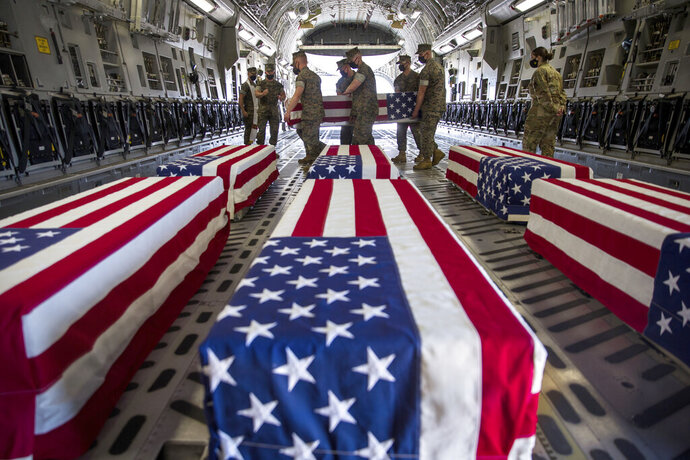 In this photo provided by the U.S. Marine Corps, U.S. Marines and sailors carry a casket inside a U.S. Air Force C-17 Globemaster III at Marine Corps Air Station Miramar, in Calif., Wednesday, Aug. 12, 2020. The remains of seven Marines and a sailor, who died after a seafaring tank sank off the coast of Southern California last month, were transferred to Dover Air Force Base in Delaware for burial preparations. (Lance Cpl. Brendan Mullin/U.S. Marine Corps via AP)