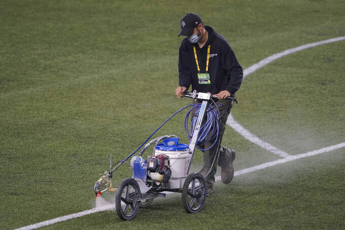 A field worker sprays a solvent to remove paint marking the goal box on the turf at CenturyLink Field following an MLS soccer match between the Seattle Sounders and Los Angeles FC, Friday, Sept. 18, 2020, in Seattle. The stadium is being prepared Sunday's NFL football game between the Seattle Seahawks and the New England Patriots. (AP Photo/Ted S. Warren)