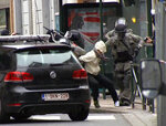 FILE - In this Friday March 18, 2016 file framegrab taken from VTM, Salah Abdeslam, centre, is arrested by police and bundled into a police vehicle during a raid in the Molenbeek neighborhood of Brussels, Belgium. Belgian prosecutors confirmed Wednesday April 27, 2016 that Paris attacks suspect Salah Abdeslam was handed over to French authorities. (VTM via AP) BELGIUM OUT