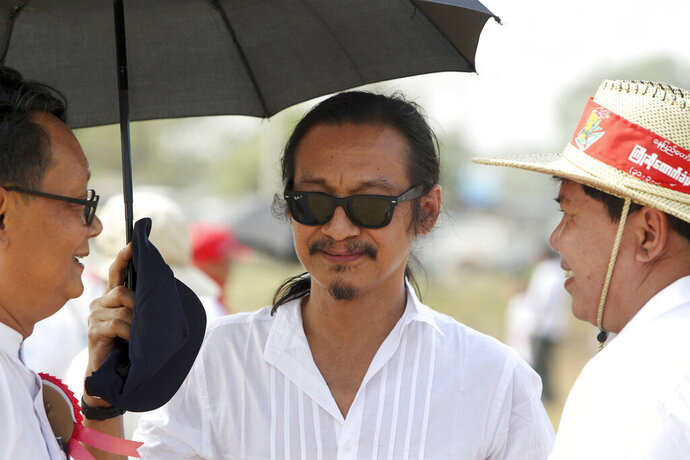 In this photo taken on March 31, 2019, Min Htin Ko Ko Gyi, center, a prominent Myanmar filmmaker, is seen during a public rally to support an amendment of the 2008 Constitution in Naypyitaw, Myanmar. On Thursday, Aug. 29, 2019, a court in Myanmar has found a prominent filmmaker guilty of defaming the military with his postings on Facebook and sentenced him to a year in prison. (AP Photo/Aung Shine Oo)