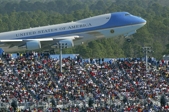 FILE - In this Feb. 15, 2004, file photo, Air Force One rises above the packed grand stands along the super stretch at Daytona International Speedway in Daytona Beach, Fla. Bush arrived before the race, talked with drivers along pit road and gave the command for drivers to start their engines. President Donald Trump will look to rev up his appeal with a key voting demographic Sunday — NASCAR fans — as he takes in the Daytona 500. (Jim Tiller/Daytona Beach News-Journal Pool via AP)