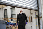 Funeral director Tom Cheeseman collects a body from a nursing home, Friday, April 3, 2020, in the Brooklyn borough of New York. He wears the shades for every call, even when it's gray and rainy. He likes that light seeps into his peripheral vision, no matter how dreary. (AP Photo/John Minchillo)