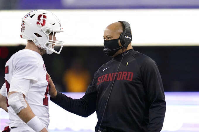 Stanford coach David Shaw, right, talks with quarterback Davis Mills during a timeout in the second half of the team's NCAA college football game against Washington on Saturday, Dec. 5, 2020, in Seattle. Stanford won 31-26. (AP Photo/Elaine Thompson)