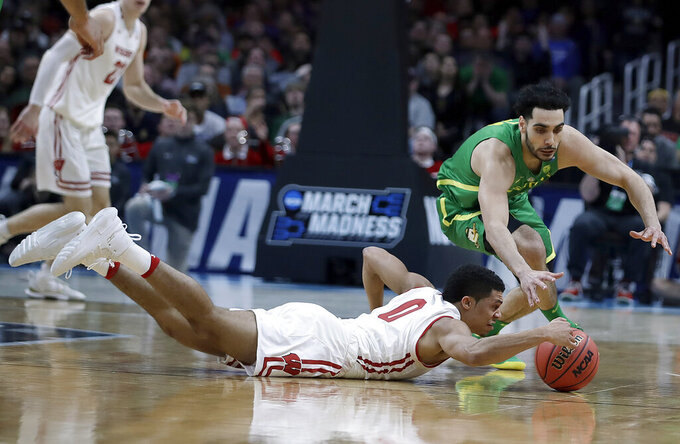 Wisconsin guard D'Mitrik Trice, bottom, reaches for the ball under Oregon guard Ehab Amin during the first half of a first-round game in the NCAA men's college basketball tournament Friday, March 22, 2019, in San Jose, Calif. (AP Photo/Ben Margot)