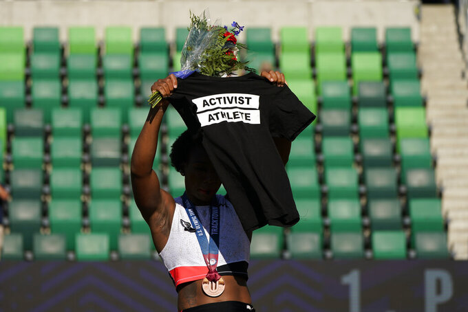 FILE - In this June 26, 2021, file photo, Gwendolyn Berry her Activist Athlete T-shirt over her head during the metal ceremony after the finals of the women's hammer throw at the U.S. Olympic Track and Field Trials in Eugene, Ore. Tommie Smith, John Carlos and Berry are among the more than 150 educators, activists and athletes who signed a letter Thursday, July 22, urging the IOC not to punish participants who demonstrate at the Tokyo Games. (AP Photo/Charlie Riedel, File)