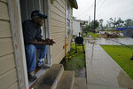 Ernest Jack, whose home was severely damaged from Hurricane Laura, sits in his front doorway as he waits for the arrival of Hurricane Delta expected to make landfall later in the day in Lake Charles, La., Friday, Oct. 9, 2020. Debris from Hurricane Laura is piled near the street. (AP Photo/Gerald Herbert)