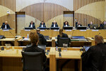 FILE - In this Monday, June 8, 2020 file photo, Presiding judge Hendrik Steenhuis, rear, fourth from left, opens the court session as the trial resumed at the high security court building at Schiphol Airport, near Amsterdam,  for three Russians and a Ukrainian charged with crimes including murder for their alleged roles in the shooting down of Malaysia Airlines Flight MH17 over eastern Ukraine nearly six years ago.  Defense lawyers for a Russian charged with involvement in the downing of Malaysia Airlines Flight 17 over eastern Ukraine in 2014 have cast doubt on prosecutors' assertions that the passenger jet was shot down by a surface-to-air missile, it was reported on Monday, June 22, 2020. (AP Photo/Robin van Lonkhuijsen, Pool, File)