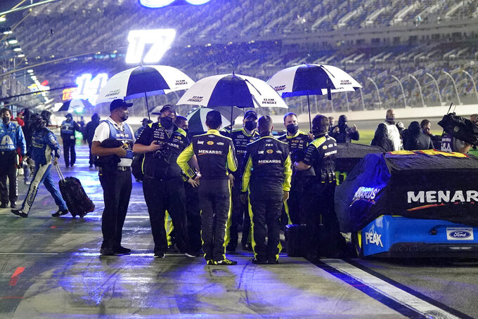 Drivers and crew members seek shelter under umbrellas as rain falls before the second of two qualifying NASCAR auto races for the Daytona 500 at Daytona International Speedway, Thursday, Feb. 11, 2021, in Daytona Beach, Fla. (AP Photo/John Raoux)