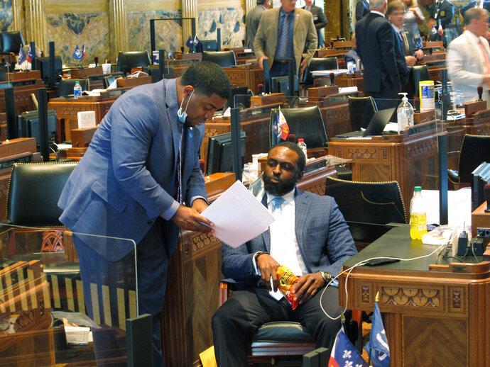Rep. Dustin Miller, D-Opelousas, left, speaks with Rep. Ted James, D-Baton Rouge, on the House floor as the Louisiana Legislature reached the final hours of its legislative session, on Monday, June 29, 2020, in Baton Rouge, La. (AP Photo/Melinda Deslatte)