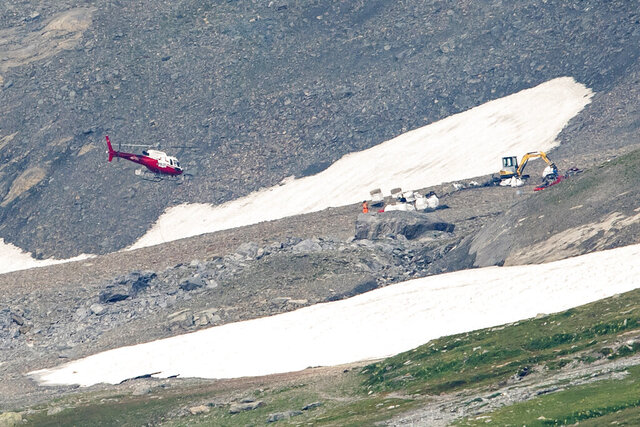 """FILE - In this Monday, August 6, 2018 file photo a helicopter flies over the site of the plane crash from Saturday afternoon near Flims, Switzerland. Swiss investigators say """"high-risk flying"""" by the pilots of a vintage propeller plane led to a 2018 crash in the Alps that killed all 20 people on board. (Ennio Leanza/Keystone via AP, file)"""