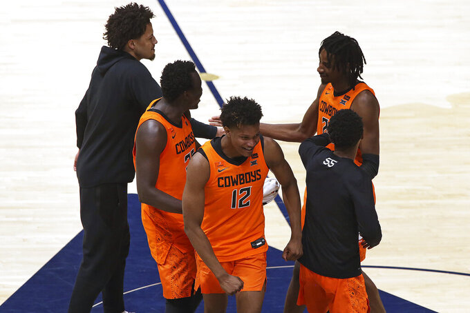Oklahoma State players celebrate after defeating West Virginia in an NCAA college basketball game Saturday, March 6, 2021, in Morgantown, W.Va. (AP Photo/Kathleen Batten)