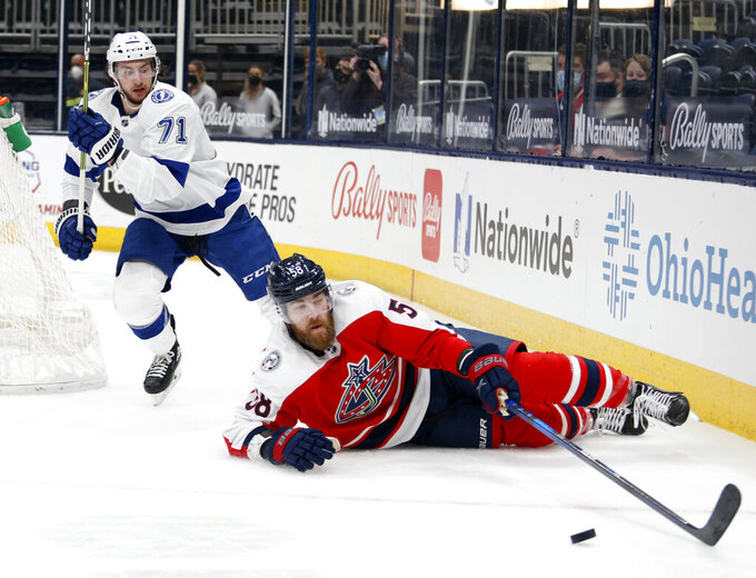 Columbus Blue Jackets defenseman David Savard, right, reaches for the puck in front of Tampa Bay Lightning forward Anthony Cirelli during the first period of an NHL hockey game in Columbus, Ohio, Tuesday, April 6, 2021. (AP Photo/Paul Vernon)