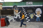 In this Nov. 7, 2019 photo, a mural depicts former F1 CEO Bernie Ecclestone, right, next to the world champion driver Lewis Hamilton, center, on the wall of a restaurant located in front of the Interlagos racetrack in Sao Paulo, Brazil. The metropolis' tourism agency says the F1 GP brought revenues of $80 million to Sao Paulo last year. (AP Photo/Nelson Antoine)