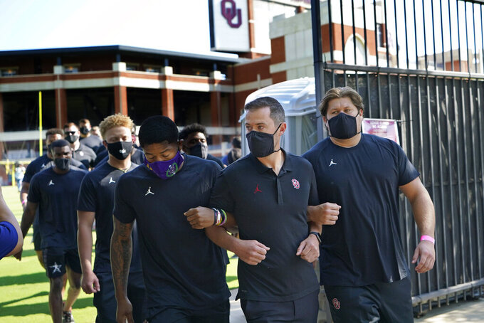 Defensive back Chanse Sylvie, left, head coach Lincoln Riley, center, and offensive lineman Creed Humphrey, right, lead the Oklahoma football team from the Gaylord Family - Oklahoma Memorial Stadium on a march to the Unity Garden to protest racial injustice in Norman, Okla., Friday, Aug. 28, 2020. (AP Photo/Sue Ogrocki)
