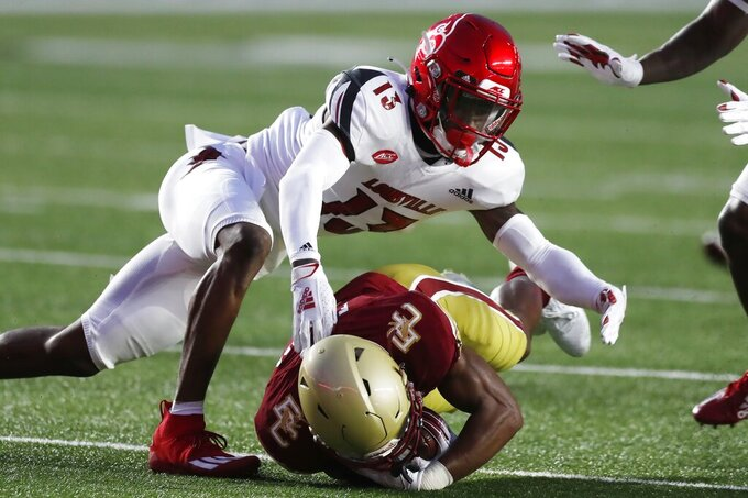 Louisville cornerback Kei'Trel Clark (13) tackles Boston College wide receiver Zay Flowers during the first half of an NCAA college football game, Saturday, Nov. 28, 2020, in Boston. (AP Photo/Michael Dwyer)