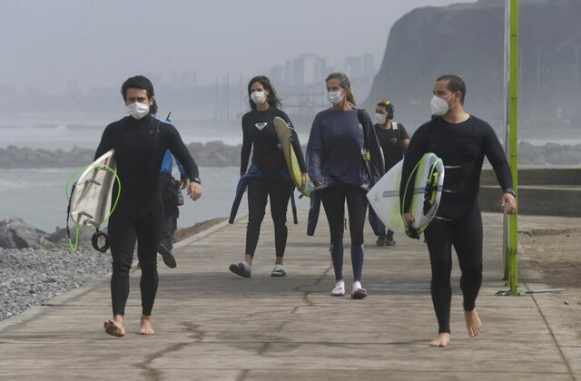 Wearing a face masks as a precaution amid the spread of the new coronavirus, surfers arrive at the reopened Waikiki beach in the Miraflores district of Lima, Peru, Thursday, June 11, 2020. The emblematic surfers who dot Peru's coastline are retaking to the waves as the hard-hit nation relaxes COVID-19 related restrictions on outdoor sports. (AP Photo/Martin Mejia)