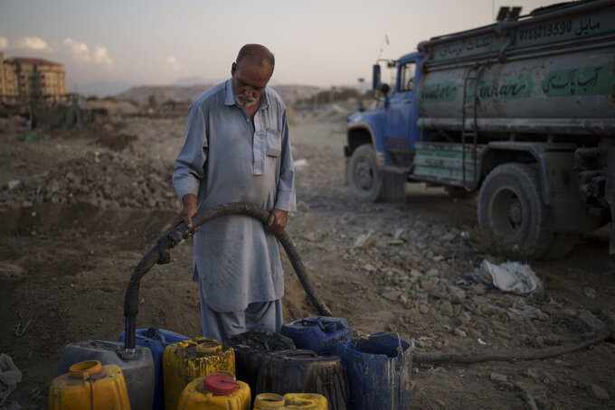 A man selling water fills containers for internally displaced people from the eastern part of the country at a poor neighborhood in Kabul, Afghanistan, Monday, Sept. 27, 2021. (AP Photo/Felipe Dana)