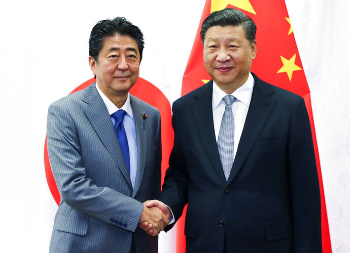 FILE - In this Sept. 12, 2018, file photo released by China's Xinhua News Agency, Chinese President Xi Jinping, right, shakes hands with Japanese Prime Minister Shinzo Abe during a meeting on the sidelines of the Eastern Economic Forum in Vladivostok, Russia. Abe is to travel to China later in October, 2018 for his first formal visit in seven years, in a further sign of improving relations between the regional rivals. (Xie Huanchi/Xinhua via AP, File)