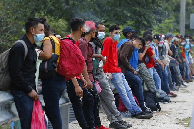 Migrants trying to reach the U.S. border rest at the edge of a highway as they await rides on passing vehicles, near Choloma, Honduras, Thursday, Jan. 14, 2021. About 200 Honduran migrants resumed walking toward the border with Guatemala early Thursday, a day before a migrant caravan was scheduled to depart the city of San Pedro Sula. (AP Photo/Delmer Martinez)