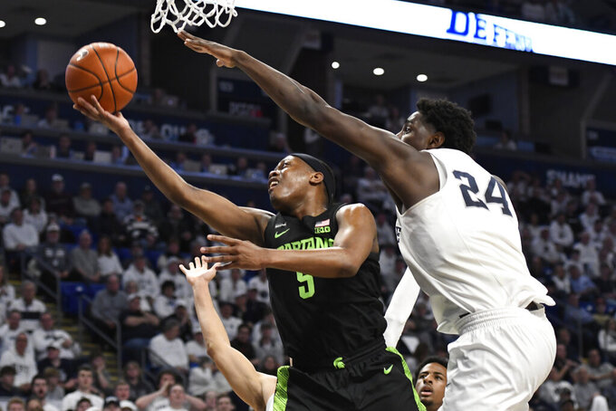 Michigan State's Cassius Winston (5) shoots as Penn State's Mike Watkins (24) defends during the first half of an NCAA college basketball game Tuesday, March 3, 2020, in State College, Pa. (AP Photo/John Beale)