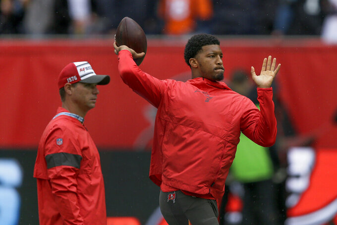 Tampa Bay Buccaneers quarterback Jameis Winston, right, warms up before an NFL football game against the Carolina Panthers, Sunday, Oct. 13, 2019, at Tottenham Hotspur Stadium in London. (AP Photo/Tim Ireland)