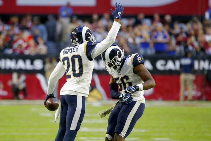 Los Angeles Rams cornerback Jalen Ramsey (20) celebrates his interception against the Arizona Cardinals with teammate defensive end Dante Fowler during the second half of an NFL football game, Sunday, Dec. 1, 2019, in Glendale, Ariz. (AP Photo/Rick Scuteri)