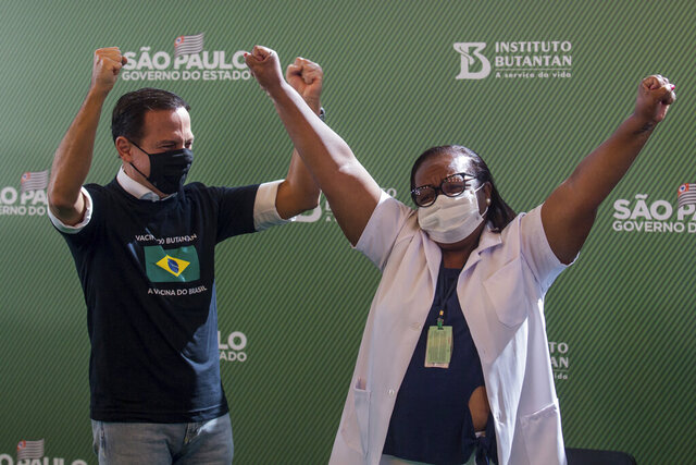 Nurse Monica Calazans, 54, and the Governor of Sao Paulo Joao Doria celebrate after she got her shot of the COVID-19 vaccine produced by China's Sinovac Biotech Ltd, at the Hospital das Clinicas in Sao Paulo, Brazil, Sunday, Jan. 17, 2021. (AP Photo/Carla Carniel)
