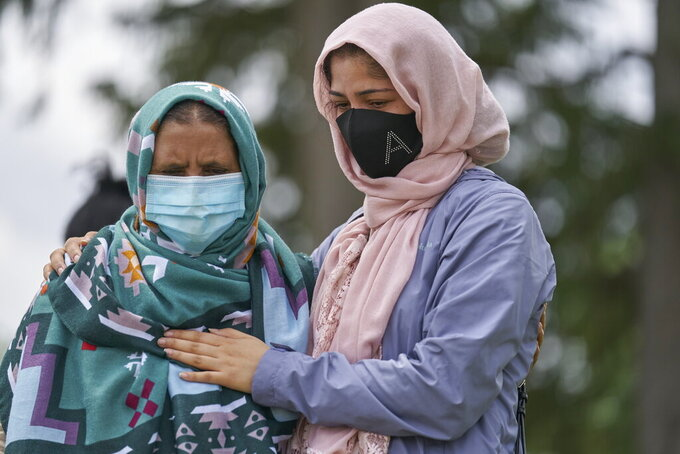 Khalida Ashram and her daughter Anila mourn at the scene of an attack on Monday, involving a driver accused of plowing a pickup truck into an immigrant family of five in London, Ontario, Tuesday, June 8, 2021.  Canadian Prime Minister Justin Trudeau has denounced the attack as police say the attack targeted Muslims.  (Geoff Robins/The Canadian Press via AP)