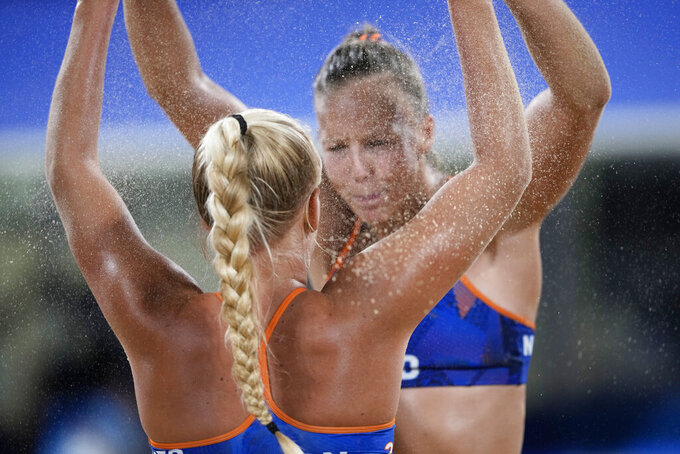 Katja Stam, right, of the Netherlands, celebrates a play with teammate Raisa Schoon during a women's beach volleyball match against Switzerland at the 2020 Summer Olympics, Monday, July 26, 2021, in Tokyo, Japan. (AP Photo/Petros Giannakouris)