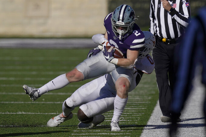Kansas State running back Harry Trotter (2) is tackled by Texas linebacker DeMarvion Overshown (0) during the second half of an NCAA college football game in Manhattan, Kan., Saturday, Dec. 5, 2020.  (AP Photo/Orlin Wagner)