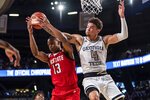 Georgia Tech guard Jordan Usher (4) and North Carolina State guard C.J. Bryce (13) go for a rebound in the first half of an NCAA college basketball game Saturday, Jan. 25, 2020, in Atlanta. (AP Photo/Danny Karnik)