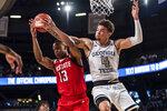 Georgia Tech guard Jordan Usher (4) and North Carolina State guard C.J. Bryce (13) go for a rebound in the first half of an NCAA college basketball game Saturday, Jan. 25, 2020, in Atlanta. (AP Photo/Danny Karnik)