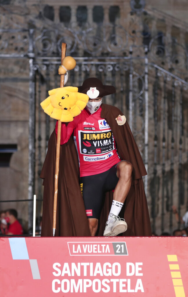 Primoz Roglic dressed as a traditional Pilgrim who walks the Way of St. James to Santiago, steps up onto the podium after winning the Vuelta Cycling race in Santiago, Spain, Sunday, Sept. 5, 2021. (AP Photo/Luis Vieira)