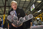Britain's Prime Minister Boris Johnson, centre, gestures with Christmas wrapping paper, during a visit to IG Design Group, wrapping paper designer and producer in Hengoed, south Wales, Wednesday, Dec. 11, 2019 on the final day of campaigning for the general election. Britain goes to the polls on Dec. 12.  (Ben Stansall/Pool Photo via AP)