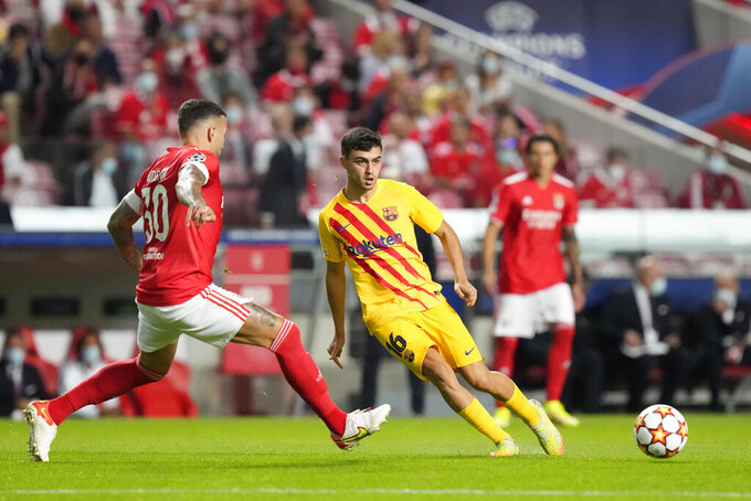 Barcelona's Pedri, centre, passes the ball challenged by Benfica's Nicolas Otamendi during a Group E Champions League soccer match between Benfica and Barcelona at the Luz stadium in Lisbon, Portugal, Wednesday, Sept. 29, 2021. (AP Photo/Armando Franca)