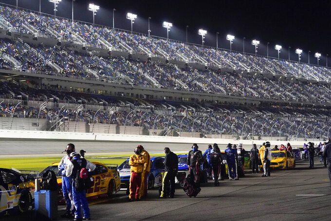 Drivers return to their cars after a weather delay during the NASCAR Daytona 500 auto race at Daytona International Speedway, Sunday, Feb. 14, 2021, in Daytona Beach, Fla. (AP Photo/John Raoux)