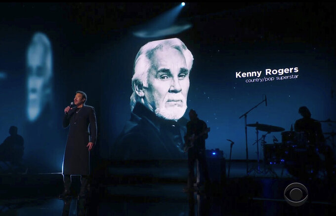 In this video grab provided by CBS and the Recording Academy, Lionel Richie performs during the In Memoriam as Kenny Rogers is pictured on screen at the 63rd annual Grammy Awards at the Los Angeles Convention Center on Sunday, March 14, 2021. (CBS/Recording Academy via AP)