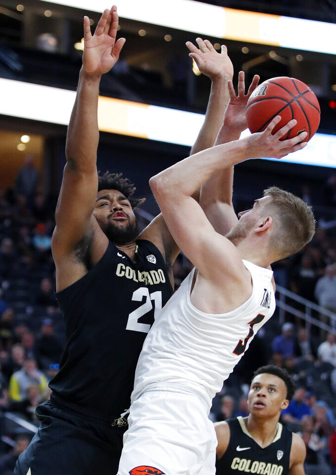 Oregon State's Tres Tinkle tries to shoot around Colorado's Evan Battey during the second half of an NCAA college basketball game in the quarterfinal round of the Pac-12 men's tournament Thursday, March 14, 2019, in Las Vegas. (AP Photo/John Locher)
