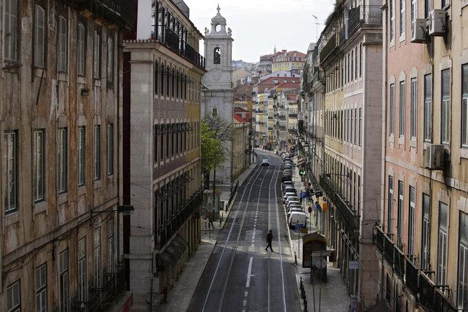 A man crosses a nearly deserted street during the coronavirus pandemic in Lisbon, Friday, April 24, 2020. (AP Photo/Armando Franca)