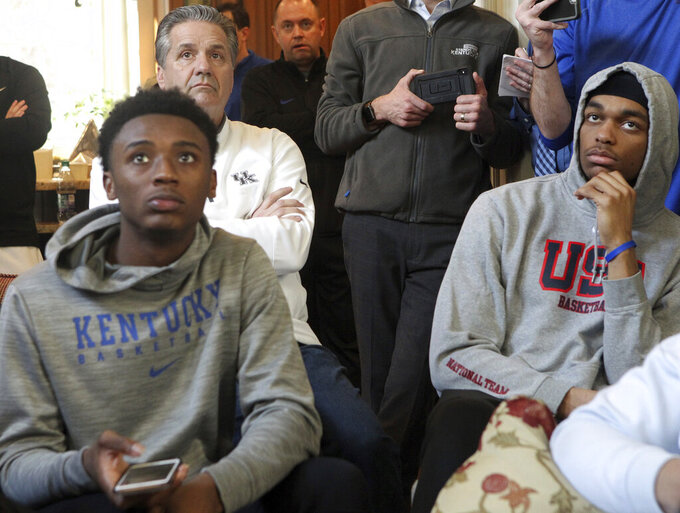 Kentucky's Ashton Hagans, coach John Calipari, left rear, and PJ Washington, right, watch the broadcast of the NCAA men's Division I college basketball tournament selection show at Calipari's home in Lexington, Ky., Sunday, March 17, 2019. (AP Photo/James Crisp)