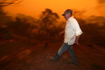 Evan Harris rushes around his property preparing to minimize fire impact at Burragate, Australia, Friday, Jan. 10, 2020, as a nearby fire threatens the area. Thousands of people are fleeing their homes and helicopters are dropping supplies to towns at risk of wildfires as hot, windy conditions threaten already fire-ravaged southeastern Australian communities. The danger is centered on Australia's most populous states, including coastal towns that lost homes in earlier fires. (AP Photo/Rick Rycroft)
